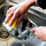 平底深锅的妇女洗涤物在KIchen水槽 图库摄影