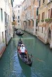 平底船的船夫乘坐在一种狭窄的渠道的长平底船,威尼斯,意大利 免版税库存图片