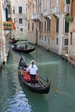 平底船的船夫乘坐在一种狭窄的渠道的长平底船,威尼斯,意大利 库存照片