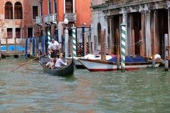 平底船的船夫在一艘长平底船的划船桨有乘客的 意大利威尼斯 免版税库存图片