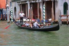 平底船的船夫在一艘长平底船的划船桨有乘客的 意大利威尼斯 库存图片