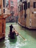 平底船的船夫在狭窄的渠道漂浮在威尼斯,意大利 库存图片