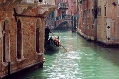 平底船的船夫在狭窄的渠道漂浮在威尼斯,意大利 免版税图库摄影
