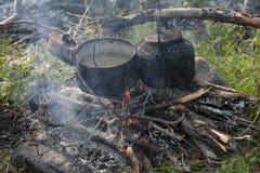 平底锅和水壶在火 免版税库存图片