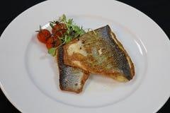 平底锅在一块白色板材的油煎的鲈鱼 免版税库存图片