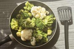 平底锅的顶视图有新鲜的被除霜的菜的:花椰菜,硬花甘蓝,抱子甘蓝 库存照片