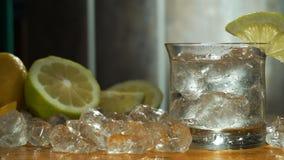 平底锅饮料、冰和柠檬在老桌上 股票视频