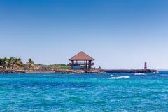 平房和一座灯塔在海滨 免版税库存图片