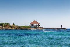 平房和一座灯塔在海滨 免版税图库摄影