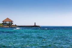 平房和一座灯塔在海滨 库存图片