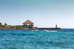 平房和一座灯塔在海滨 免版税库存照片