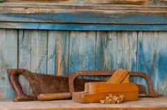 整平机、引形钢锯和一把锯在老木背景,芯片 免版税库存照片