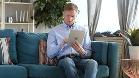 平板电脑的中世纪人浏览互联网,坐长沙发 影视素材