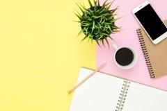 平的一个工作空间的位置顶视图与白色空白的笔记本页、咖啡杯和嘲笑的在淡色背景的电话 免版税库存照片
