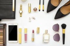 平的与米黄高跟鞋鞋子、太阳镜和化妆用品的位置女性辅助部件拼贴画在白色背景设置了 文本空间 是 库存照片