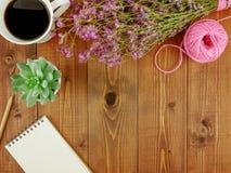 平的位置、顶视图褐色木书桌有文具的和咖啡 免版税库存图片