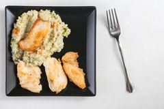 平的位置上面炸鸡白肉用在黑角规板材的意大利煨饭在白色大理石 免版税库存照片