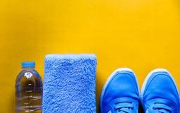 平的位置体育鞋子,瓶水,在黄色背景的毛巾 免版税库存照片