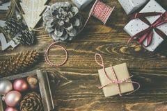 平的位置在土气年迈的木背景、圣诞节或者新年在工艺褐色白皮书包裹的gits 丝带,麻线,杉木锥体 库存照片