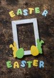 平的位置复活节背景 空的框架,在木土气背景,顶视图的纸自创兔子 复活节装饰 免版税库存图片