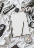 平的位置妇女辅助部件背景 空白的笔记薄,笔,玻璃,手表,染睫毛油,电话,耳机,在一轻的backgrou的香水 免版税库存照片