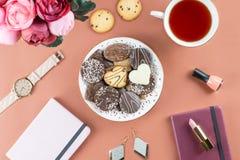 平的位置家庭办公室书桌 与日志,花,甜点,时装配件的女性工作区 时尚博客作者概念 库存照片