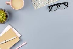 平的位置家庭办公室书桌 与笔记本,镜片,茶杯子,日志,植物的女性工作区 复制空间 免版税库存图片