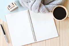 平的位置或灰色顶视图编织了围巾、开放空白的笔记本纸、咖啡杯和新年立方体日历在木背景 图库摄影