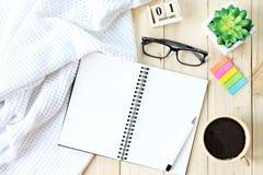 平的位置或白色顶视图编织了毯子、开放空白的笔记本纸、咖啡杯和新年立方体日历在木backgro 免版税图库摄影