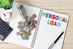 平的位置或词`在开放空白的笔记本纸的个人贷款`顶视图和硬币从玻璃瓶子驱散了 库存照片