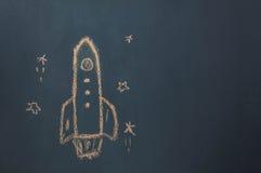 平的位置手工制造图画火箭船发射/离开对与星的空间在黑板由粉笔板 免版税库存照片