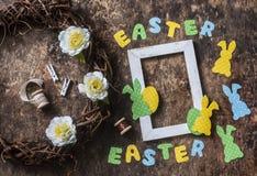 平的位置手工制造复活节装饰-藤花圈与花,纸兔子,丝带,在木背景的空的框架, t的 图库摄影