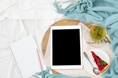 平的位置早餐在床上用莓乳酪蛋糕、薄荷的茶和开放笔记本,片剂 免版税库存照片