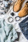 平的位置春天妇女` s衣物设置了-绒面革起动,毛线衣,牛仔裤,围巾,在轻的背景的辅助部件 免版税库存照片