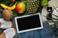 平的位置构成用热带水果菠萝芒果在大棕榈叶的香蕉椰子 妇女牛仔裤短裤拖鞋帽子 免版税库存图片