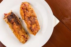 平的位置油煎了在棕色包伙食上的白色板材供食的鸡蛋的烤辣椒粉 免版税库存照片