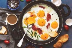 平的位置煎蛋用在平底锅的蕃茄,多士用黄油,咖啡 在蓝色背景的一顿热诚的早餐 免版税库存照片
