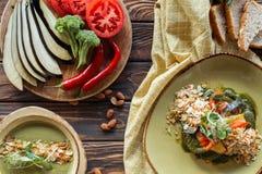 平的位置用素食沙拉、奶油色汤和被安排的新鲜的成份在木桌面 免版税库存照片