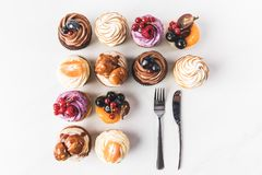 平的位置用被安排的各种各样的甜杯形蛋糕和利器 库存图片
