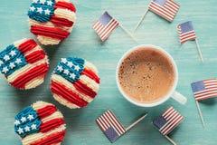 平的位置用被安排的杯形蛋糕、咖啡和在木桌面的美国国旗 库存图片