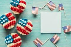 平的位置用被安排的杯形蛋糕和美国国旗在木桌面 免版税库存图片