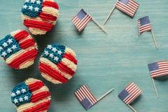 平的位置用被安排的杯形蛋糕和美国国旗在木桌面 库存照片