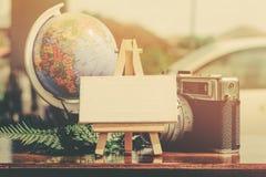 平的位置结构的葡萄酒照相机、指南针、绿色植物和字组在木桌理想假期和旅行概念的 库存照片