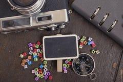 平的位置结构的葡萄酒照相机、指南针、计划者书和字组在木桌上 免版税库存图片