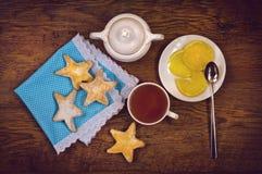 平的位置茶、饼干以星的形式和柠檬在木桌上 图库摄影