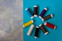 平的位置针线包,剪刀,螺纹,在蓝色背景的卷尺多彩多姿的短管轴  免版税库存照片