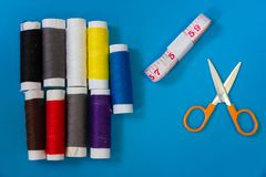 平的位置针线包,剪刀,螺纹,在蓝色背景的卷尺多彩多姿的短管轴  图库摄影