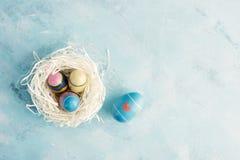 平的位置顶视图白皮书巢用三个葡萄酒复活节彩蛋和一个蓝色鸡蛋与红色心脏在蓝色背景 库存照片