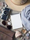 平的位置,顶视图旅客` s笔记本,帽子太阳镜,照相机,香水 免版税库存照片