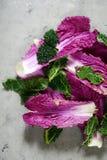 平的位置 北京,皱叶甘蓝和莴苣叶子在灰色背景 季节性菜 沙拉叶子 免版税库存图片